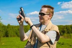 从体育枪的人射击 免版税库存照片