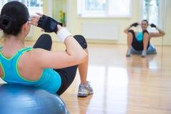 体育概念-做在bosu球的年轻运动的妇女锻炼 免版税库存图片