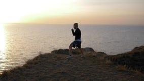 体育活动,肌肉拳击手人在小山的冠军前履行打击在海附近 影视素材