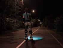 体育滑冰在晚上的路辗女孩使用手电或火炬 库存照片