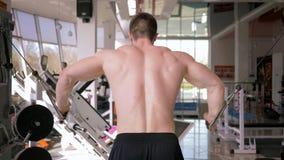体育生活方式,做在胳膊的肌肉的肌肉运动员力量锻炼在牵引模拟器的在健身房锻炼 股票录像