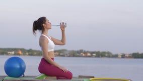 体育生活方式,年轻可爱的运动妇女喝从瓶的矿物清楚的水,当做体育时并且享用 股票视频