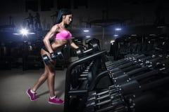 体育穿戴的健身妇女与在健身房的完善的性感的身体 免版税库存图片