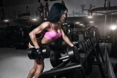 体育穿戴的健身妇女与在健身房的完善的性感的身体 免版税库存照片