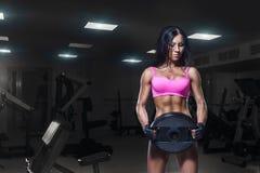 体育穿戴的性感的健身妇女与在健身房的完善的健身身体 库存照片