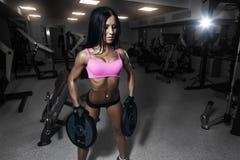 体育穿戴的性感的健身妇女与在健身房的完善的身体 免版税库存图片