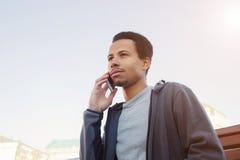 体育穿戴的年轻人谈话在手机 户外人 图库摄影