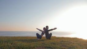 体育紧接结合同时蹲下在山的日落期间反对一个美好的风景 股票录像