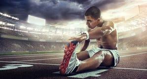 体育背景 舒展在起动线的赛跑者 库存图片