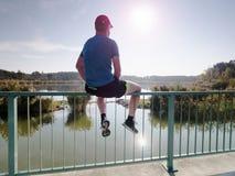 体育衣物的唯一人坐桥梁扶手栏杆 免版税库存照片