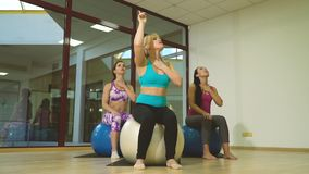 体育衣裳的三名妇女坐瑜伽的球并且伸出他们的舌头和拔,训练从 影视素材