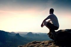 黑体育裤子和灰色衬衣的年轻人坐峭壁的边缘并且看对有薄雾的谷轰鸣声 免版税库存图片