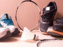 体育设置了黑橙色体育鞋子和蓝色体育鞋子和shuttlecocks与两羽毛球拍在体育背景在conce 库存照片