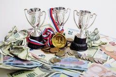 体育赢取的概念:在不同的货币欧元,美元, rubl,金牌第一个地方中的三个杯子 库存图片
