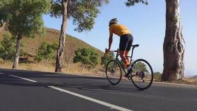 体育路自行车的一个人在山的路被找出的上流乘坐 在慢动作 股票录像