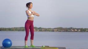体育蹲,有执行健身锻炼的美好的身体的训练的年轻女人在体育期间本质上在桥梁的 股票录像
