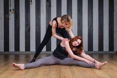 体育运动二妇女 健身讲师查出的白色 与教练员的教训 做舒展回到帮助的两名妇女完成 免版税库存图片