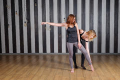体育运动二妇女 健身讲师查出的白色 与教练员的教训 做舒展回到帮助的两名妇女完成 库存图片