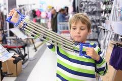 体育运动的男孩购物尝试金属肩膀扩展器 免版税库存图片