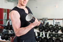 体育运动-人执行与在健身房的杠铃 免版税库存照片