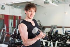 体育运动-人执行与在健身房的杠铃 免版税图库摄影