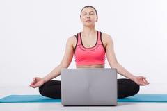 体育运动 健身瑜伽妇女 使用膝上型计算机和互联网通信,一名中年妇女举办瑜伽训练 免版税库存图片
