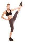 体育运动 舒展腿的健身运动的白肤金发的女孩被隔绝 免版税库存照片
