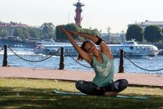 体育配件的美丽的女孩在圣彼德堡穿衣和做健身或瑜伽在江边的耳机 免版税库存照片