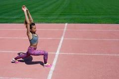 体育锻炼和舒展在体育场内 一双灰色T恤杉、桃红色裤子和运动鞋的一个年轻深色皮肤的女孩培养了她的ha 免版税图库摄影