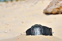 体育防水在沙子忘记的手表 库存照片