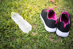 体育鞋子和瓶在草背景的水 炫耀辅助部件 免版税库存图片