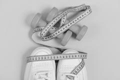 体育鞋子和设备健康形状的 健身和运动服概念 有测量的磁带的运动鞋 库存照片