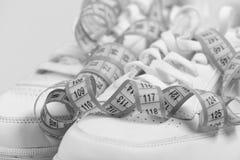 体育鞋子和设备适合形状的 跑步和健康生活方式概念 有测量的磁带的运动鞋 库存照片