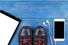 体育鞋子顶视图用片剂计算机和手机有屏幕和耳朵耳机和白色空的空白的 免版税库存照片