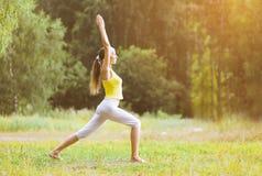 体育,健身,瑜伽-概念,做锻炼的妇女户外 免版税库存图片