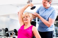 体育锻炼的资深妇女在与教练员的健身房 免版税库存照片