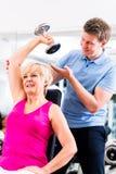 体育锻炼的资深妇女在与教练员的健身房 库存照片