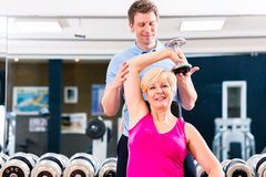 体育锻炼的资深妇女在与教练员的健身房 免版税库存图片
