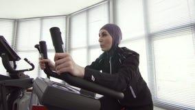 体育hijab的女子运动员在自行车模拟器 股票录像