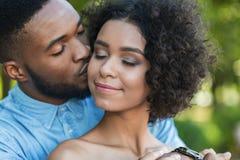 体贴亲吻他的面颊的英俊的人女朋友 免版税库存图片