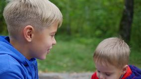 体贴拥抱和亲吻他的更老的兄弟的小婴孩 拥抱他的弟弟的男孩 影视素材