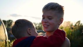 体贴拥抱和亲吻他的更老的兄弟的小婴孩 拥抱他的弟弟的男孩 股票录像