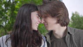体贴摩擦他们鼻子和亲吻的逗人喜爱的年轻夫妇画象接近  愉快的女孩和男孩消费时间 影视素材
