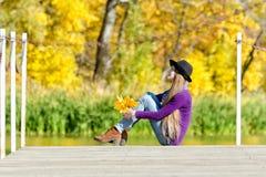 体贴的女孩坐有秋叶的船坞在手上 晴朗的日 免版税库存图片