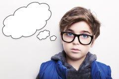 体贴的年轻与空的想法泡影的男孩佩带的玻璃 免版税库存图片