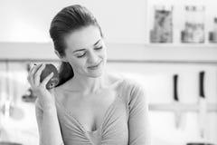体贴的年轻主妇用苹果在现代厨房里 库存照片