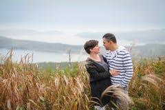 体贴看彼此的爱恋的有吸引力的中年夫妇在秋天草 库存图片