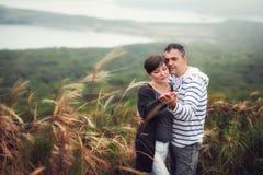 体贴看彼此的爱恋的有吸引力的中年夫妇在秋天草 免版税图库摄影