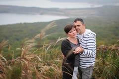 体贴看彼此的爱恋的有吸引力的中年夫妇在秋天草 免版税库存照片