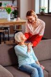 体贴palming母亲手和拿着头的愉快的成人夫人 免版税库存图片